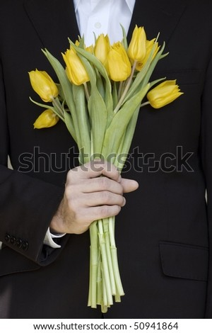 man in a suit holding bunch of yellow tulips - stock photo