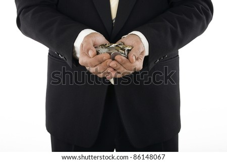 man in a suit holding coins from around the world - stock photo