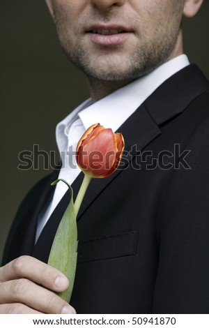 man in a suit holding one red tulip - stock photo