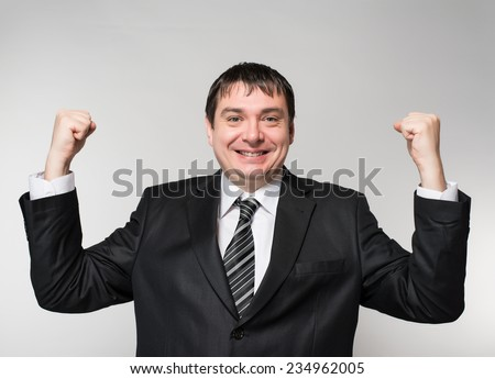man in a suit raised both hands up the joy of victory delight