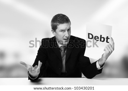 man in a suit sat at a desk look at a  piece of paper with the word debt printed on it
