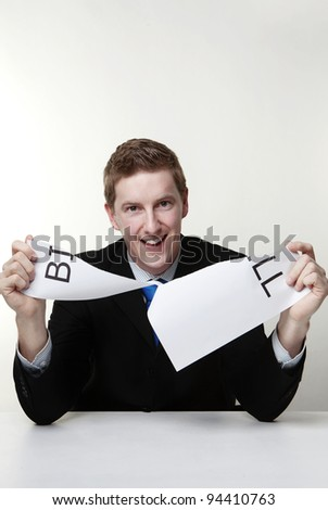 man in a suit sat at a desk ripping a  piece of paper up with the word bill printed on it and looking happy doing so. - stock photo