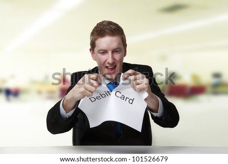 man in a suit sat at a desk ripping a  piece of paper up with the words debit card printed on it and looking happy doing so. - stock photo
