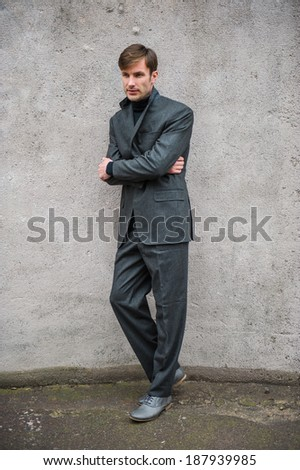 Man in a suit standing at the wall and thinking - stock photo
