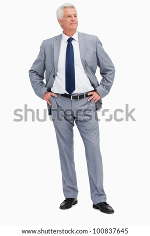 Man in a suit with his hands on his hips against white background