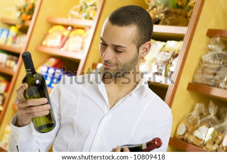 man in a supermarket comparing two wines - stock photo