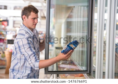 Man in a supermarket standing in front of the freezer looking for his favorite frozen food - stock photo