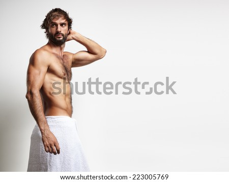 man in a towel touching his head - stock photo