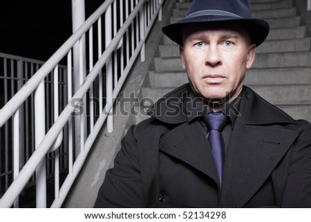 Man in a trench coat and hat