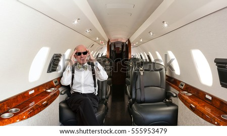 Man in a tuxedo expressing discomfort inside a private jet