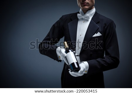 Man in a tuxedo with a bottle wine - stock photo