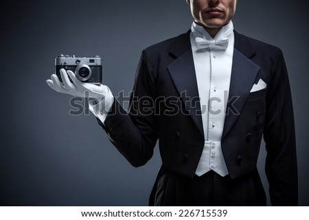 Man in a tuxedo with camera - stock photo