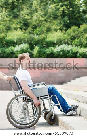 Man in a wheelchair in front of the stairs - stock photo