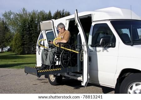 man in a wheelchair uses a wheelchair lift - stock photo