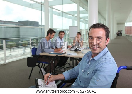 Man in a wheelchair working in an office - stock photo