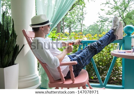 Man in a white hat and with glass of wine resting on the summer terrace - stock photo