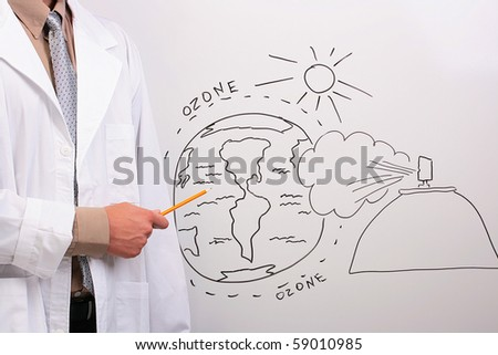 Man in a white lab coat pointing to a drawing of the earth being in danger. - stock photo