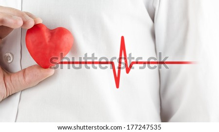 Man in a white shirt holding a red heart depicting a healthy heart and good health. - stock photo