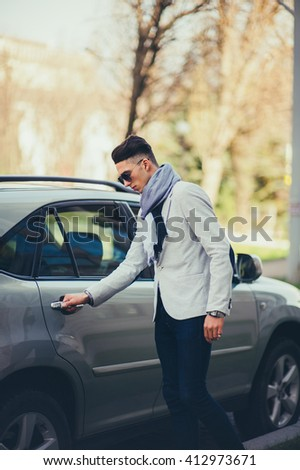 Man in a white suit and glasses waiting on the street near the car