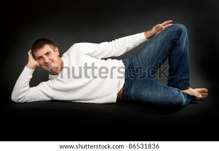 man in a white sweater lying on a black background