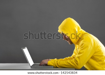 man in a yellow jacket working on the Internet. on gray background