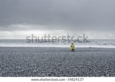 man in a yellow rain coat kneeling down at the ocean - stock photo