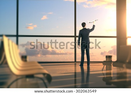 man in airport with airplane in hand - stock photo