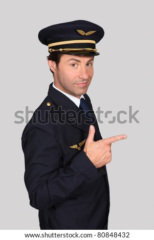 Man in an airline captain's uniform pointing the way