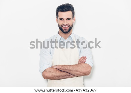 Man in apron. Confident young handsome man in apron keeping arms crossed and smiling while standing against white background  - stock photo
