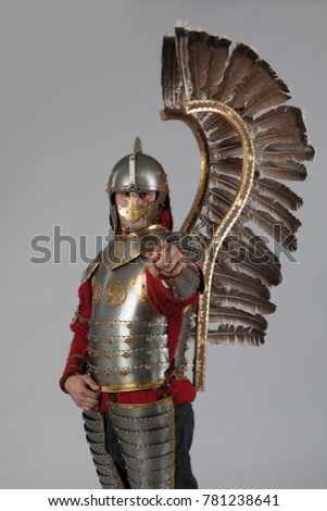 Man in armor of hussar legion posing on gray background.  Character for computer game.