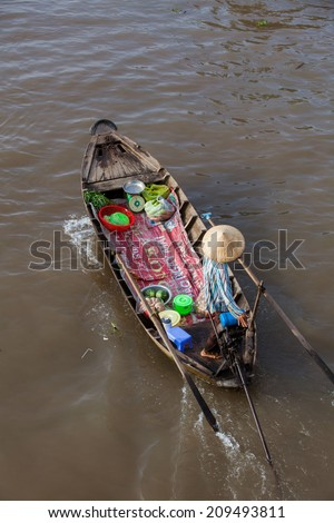 Man in asian conical hat is floating down Mekong river on wooden boat, Can Tho Floating Market, Mekong Delta, Vietnam.