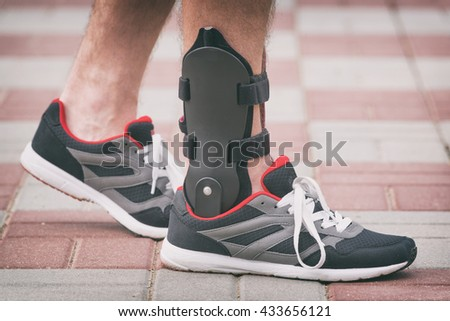 Man in athletic sneakers wearing ankle orthosis or brace - stock photo