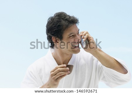 Man in bathrobe drinking tea and using cell phone