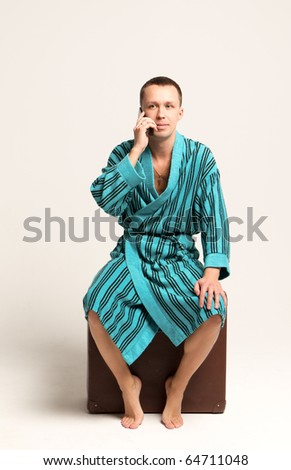 man in bathrobe is talking on the phone