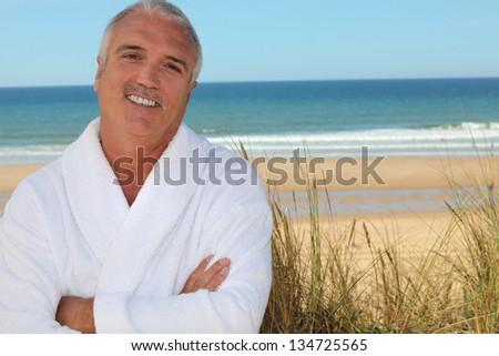 Man in bathrobe on beach - stock photo