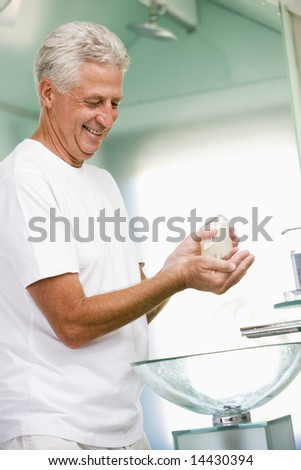 Man in bathroom applying aftershave and smiling - stock photo