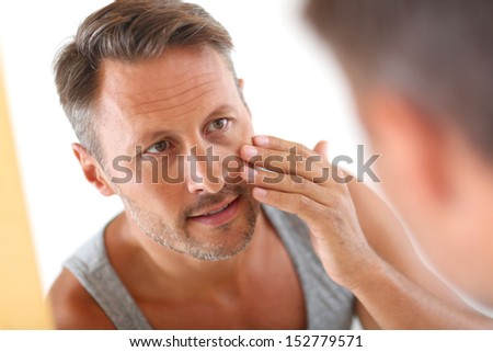 Man in bathroom applying cosmetics on his face - stock photo
