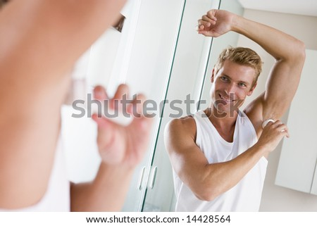 Man in bathroom applying deodorant smiling