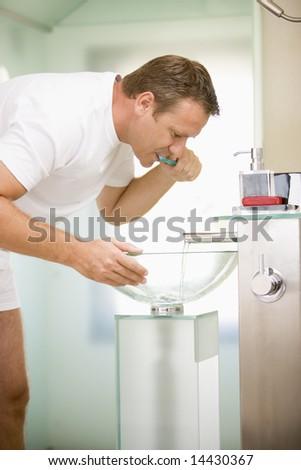 Man in bathroom brushing teeth - stock photo