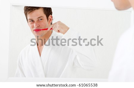 Man in bathroom brushing teeth and smiling - stock photo
