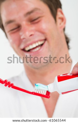 Man in bathroom putting toothpaste on toothbrush - stock photo