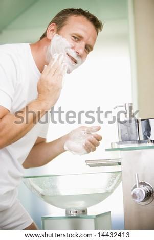 Man in bathroom shaving - stock photo