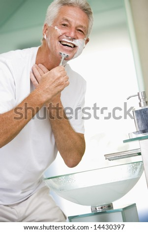 Man in bathroom shaving and smiling - stock photo
