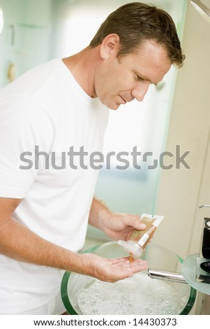 Man in bathroom with hair gel - stock photo
