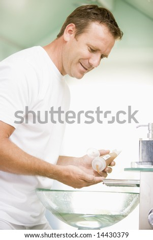 Man in bathroom with hair gel smiling - stock photo