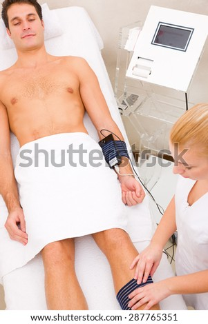 man in beauty center having muscle mass check - stock photo