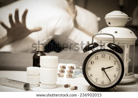 Man in bed want tablets and drugs suffering insomnia, hangover and headache at night - stock photo