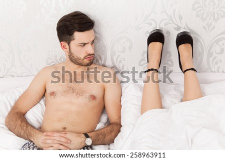 Man in bed wondering about the lying position of his girlfriend - stock photo