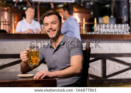 Man in beer pub. Cheerful young man holding a beer mug and smiling while sitting in bar