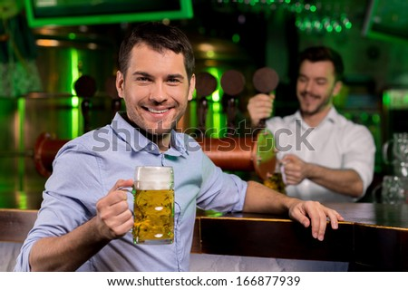 Man in beer pub. Handsome young man holding a beer mug and smiling while bartender pouring beer on the background - stock photo